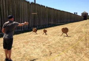 A visitor throwing trade axes inside the Heritage Area